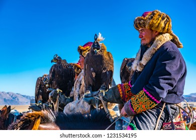 ULGII, MONGOLIA - OCTOBER 6, 2018 : Golden Eagle Festival. The Mongolian Horsemen on the horseback in traditional clothing with eagle in their hand ready for the competition at Ulgii in Mongolia