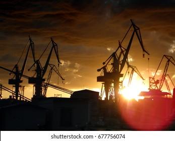 Uljanik dock with silhouettes of giant cranes against orange  cloudy sunset, Pula, Croatia.