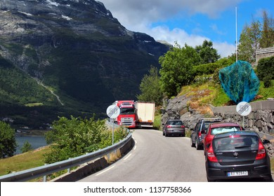 Ullensvang, Norway - June 22, 2018: Traffic jam on a narrow coastal road. Cars are waiting for the trucks to pass each other on a roadway along Hardanger fjord.