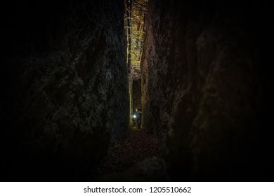 The Ultimate Cave Explorer. Caucasian Men in His 30s in the Narrow Section of the Cave. Fall Foliage in the Background.