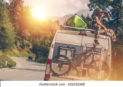 The Ultimate RV Vacation. Camper Van Traveling with Kayak and Mountain Bike. Relaxing Men Seating on the Motorhome Roof.