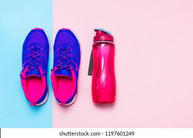 Ultra blue violet pink female sneakers and water bottle on pastel pink background flat lay top view with copy space. Sports shoes, fitness, concept of healthy lifestile, everyday training.