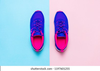 Ultra blue violet pink female sneakers on pastel pink blue background flat lay top view with copy space. Sports shoes, fitness, concept of healthy lifestile, everyday training.