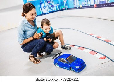 ULTRA MALL, UFA, RUSSIA, 21 AUGUST, 2017: Little boy with his mother playing with radio remote controlled car at the training ground