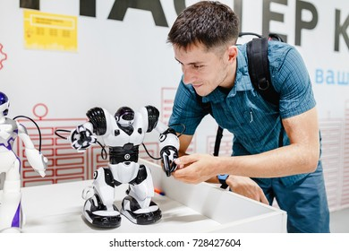 ULTRA MALL, UFA, RUSSIA, 21 AUGUST, 2017: A young man looks at a robot made of a block designer with automated control. Concept of technologies and engineering