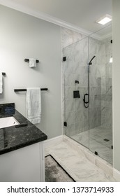 Ultra modern bathroom with glass shower and marble and granite tile and sink.