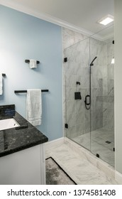 Ultra modern bathroom with glass shower and marble and granite tile and sink and blue wall.