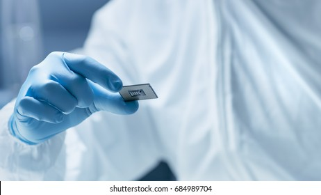 In Ultra Modern Electronic Manufacturing Factory Design Engineer in Sterile Coverall Holds Microchip with Gloves and Examines it.