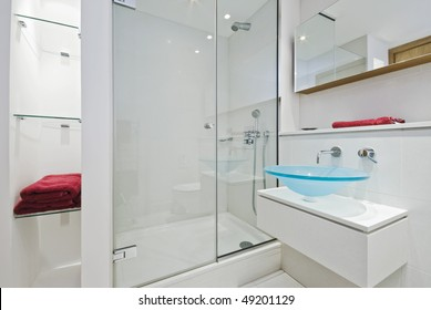ultra modern luxurious en-suite bathroom with shower cabin and glass hand wash basin