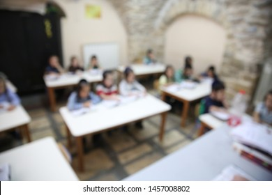 Ultra orthodox Jewish boys sit at their desks and listen to a lecture them, blurred