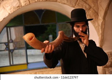 Ultra orthodox Jewish man holds and blows a Shofar (rams horn), a symbol of Rosh Hashana holiday, on a background of a stone wall with stained glass window. Focus on horn.