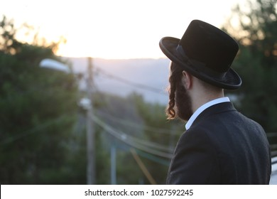 Ultra orthodox Jewish man meditates in prayer while staring into the sunset behind the mountains