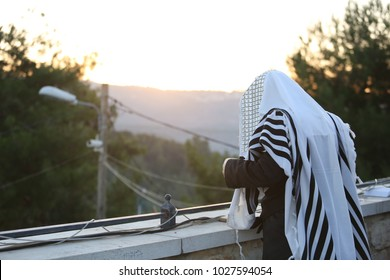 Ultra Orthodox Jewish man prays near wall  with sunset in the mountains in the backround
