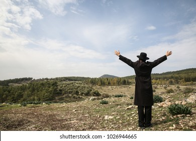 Ultra orthodox Jewish man raises his hands in prayer to God in field