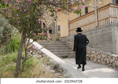 Ultra orthodox Jewish man walks up stairs between homes and buildings in Israel