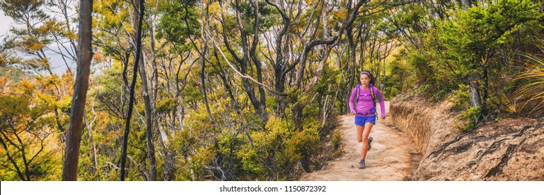 Ultra running race trail competition athlete woman runner on long distance marathon through forest and mountains in New Zealand, banner panorama.