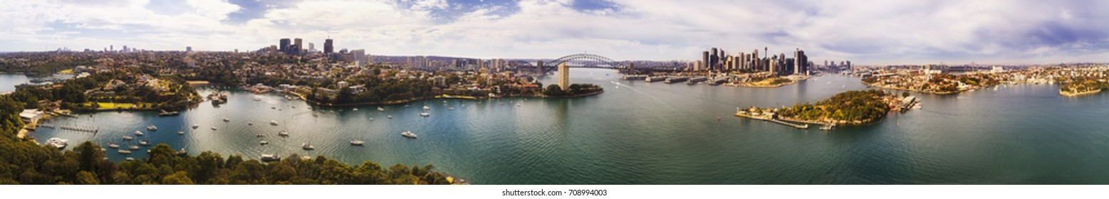 Ultra wide aerial panorama of Great Sydney area from Lower North shore through the Sydney Harbour Bridge to city CBD, Darling Harbour and inner West suburbs on shores of harbour waters.