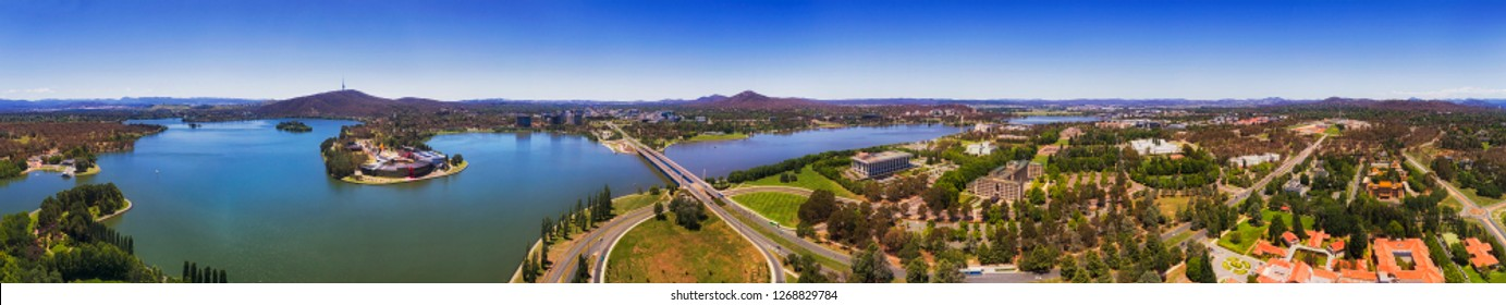 Ultra wide aerial panorama over Canberra capital city of Australia from parliament house on the hill to distant TV tover behind BUrley Griffin lake.