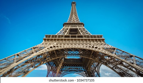 Ultra wide angle of Eiffel Tower over blue sky in Paris, France. Worms eye view of the entire monument