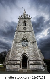 ultra wide angle image of a marble church entrance and spire with a threatening sky in the background