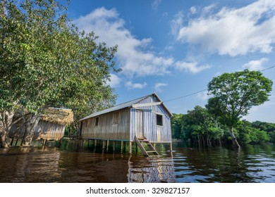 Ultra wide angle view of wooden house built in Amazon rainforest over black river, Brazil