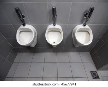 Ultra wide top view of 3 white automatic ceramic urinals on Grey tiled wall in an public toilet