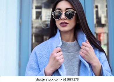 Ultra-fashion concept. young woman of fashion wearing blue coat and posing over blue glass urban background. Street style. businesswoman. outdoors. fashionable accessories.