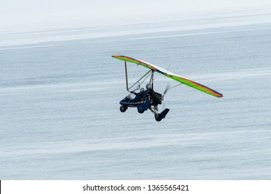 An ultralight trike flies over the Atlantic ocean off the coast of Amelia Island, Florida.  The trike is a type of powered hang glider, where flight is controlled by weight-shift.