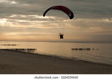 Ultralight trike over the sea at sunset.