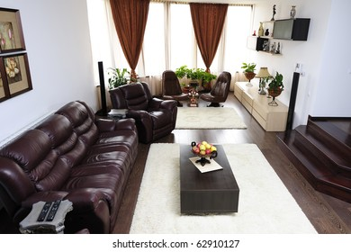 Ultra-modern living-room with leather sofa and armchairs near big windows with curtains