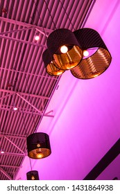 Ultra-modern loft style in purple toned color decorative lamps and lampshades hang on long rope, industrial ceiling, interior design, vertical frame