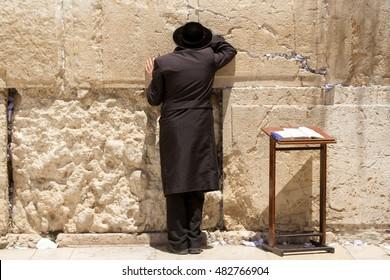 Ultra-orthodox man in black praying at the Wailing Wall, Jerusalem