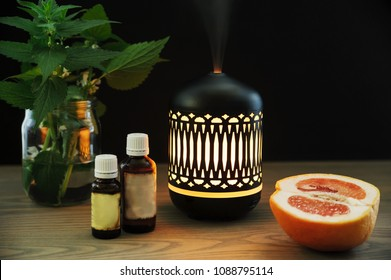 The ultrasonic aroma diffuser is made in oriental style. There are aromatic oils, half a grapefruit near the diffuser on the table.