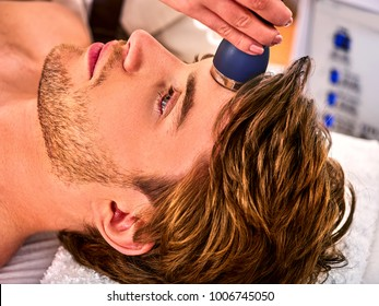 Ultrasonic facial treatment on ultrasound face machine electric lift massage spa salon. Stimulation male muscles. Professional microcurrent therapy .