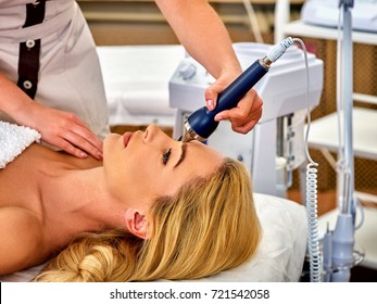 Ultrasonic facial treatment on ultrasound face machine. Woman taking electric lift massage spa salon. Stimulation muscles on professional equipment microcurrent therapy. New methods of rejuvenation.