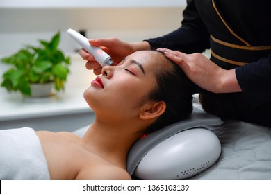 Ultrasonic facial treatment ultrasound face machine. Woman receiving electric lift massage spa salon. Electronic stimulation female muscles. Improvement of skin condition