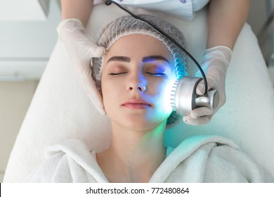 Ultrasonic massager. Light skin treatment, the woman in the beauty salon