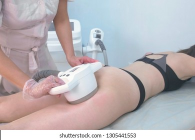 Ultrasound cavitation body contouring treatment. Woman getting anti-cellulite and anti-fat therapy for buttocks in beauty salon.