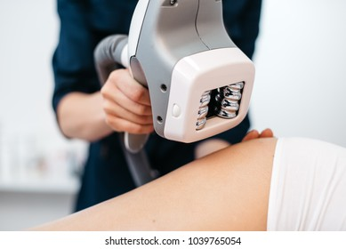 Ultrasound cavitation mashine in the hands of beautician. Close-up view. Woman is receiving the anti-cellulite treatment. Body contouring. No face.