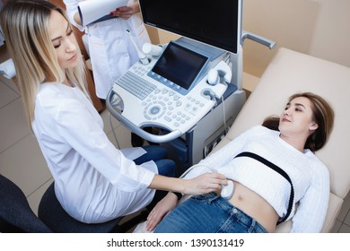 Ultrasound examination of the abdomen in the medical clinic. Woman doctor conducts research for a young blonde.
