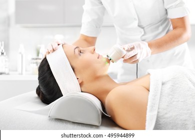 Ultrasound infrared light cosmetic treatment for the face. Light skin treatment, the woman in the beauty salon