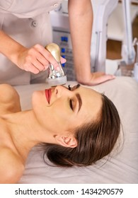 Ultrasound therapy for skin tightening in beauty spa salon. Beautician does procedure by electric device.
