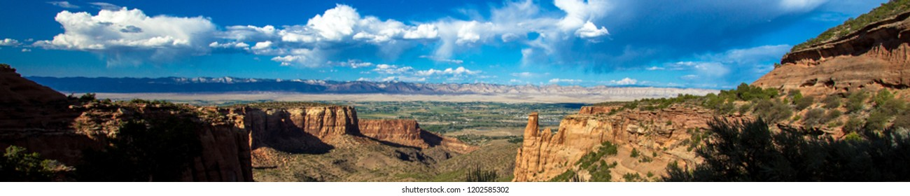 Ultra-wide panorama of Colorado National Monument and the landscape to the east, with dramatic cloud formations