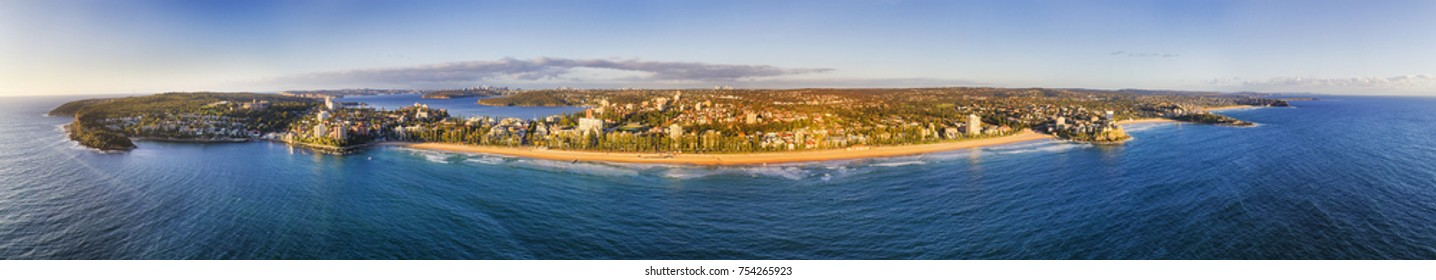 Ultra-wide panorama of Sydney Northern beaches from Manly sandy beach and North Head to North with Sydney CBD and Harbour in the background in elevated aerial view.