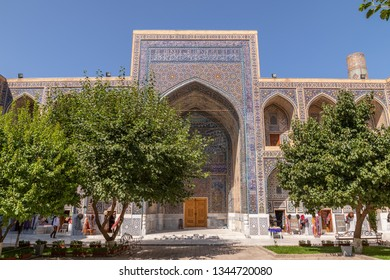 The Ulugh Beg madrasah view from the yard.  In the courtyard of the Madrasah with trees. Inside the Madrasah on Registan square in Samarkand. Ancient Madrasah in Uzbekistan. Sunny summer day.