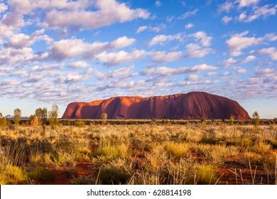 ULURU, AUSTRALIA - CIRCA AUGUST 2016: Uluru at sunrise under beautiful fluffy clouds, Uluru-Kata Tjuta National Park, Northern Territory, Australia