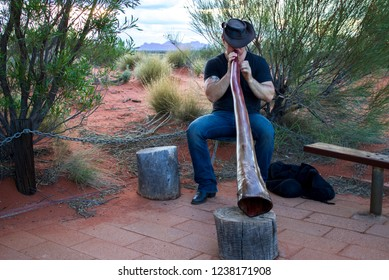 Uluru Kata Tjuta National Park, Northern Territory, Australia - 01.06.2018: A man plays a didgeridoo surrounded by red desert sand. Kata Tjuta (The Olgas) can be seen in the background.