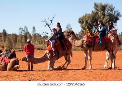 ULURU, NORTHERN TERRITORY, AUSTRALIA - 15 JUNE 2014: Tourists dismounting at the Uluru Camel Farm following an early morning camel trek through the red desert sands around Uluru.