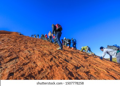 Uluru, Northern Territory, Australia - Aug 23, 2019: crowd of people climbing on Ayers Rock in Uluru - Kata Tjuta National Park before 26 October 2019 when the climb will be closed permanently.