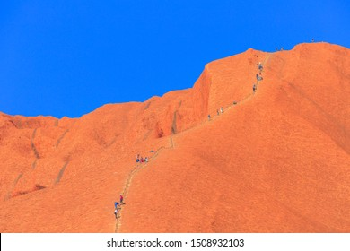 Uluru, Northern Territory, Australia - Aug 23, 2019: people climb on Ayers Rock. Climbing Uluru is sacred to Anangu people, the traditional owners of Uluru-Kata Tjuta and very dangerous.
